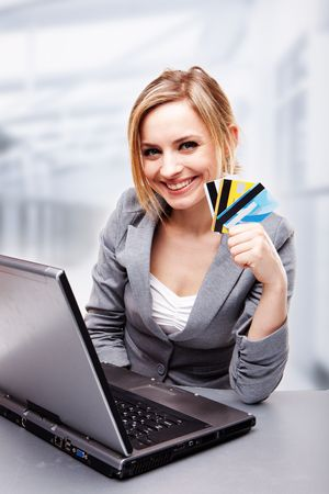 Businesswoman smiling and holding credit cards