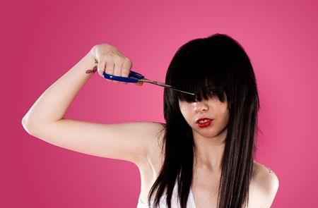 young woman cutting her fringe over pink background photo
