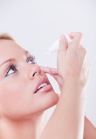 irritated: woman`s eye and eyedropper with waterdrop on tip