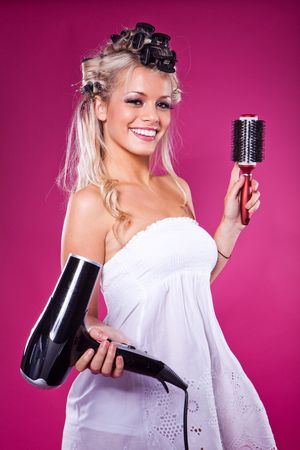 Beautiful smiling woman drying her hair with a blow dryer on pink  photo