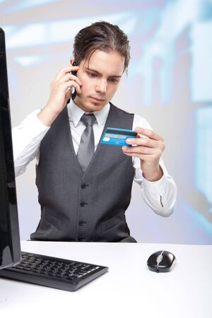Business man in his office and a credit card on the phone photo