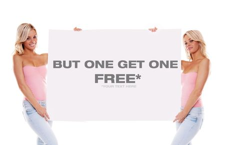 holding a sign: sexy twin girls holding a billboard add isolated over a white background Stock Photo