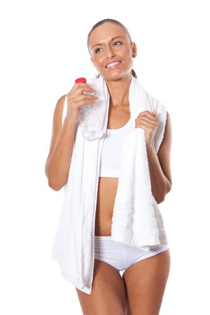 Portrait of cute young woman with water bottle in hand and towel around her neck photo