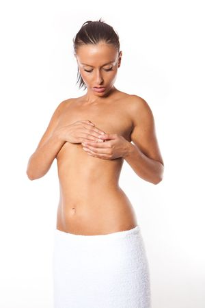 nude young: Young Caucasian adult woman examining her breast for lumps or signs of breast cancer
