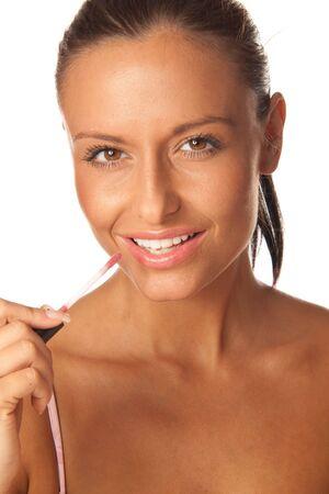 Beautiful young woman applying red lip gloss Stock Photo - 7726599