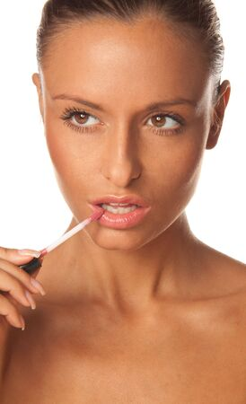 Beautiful young woman applying pink lip gloss photo
