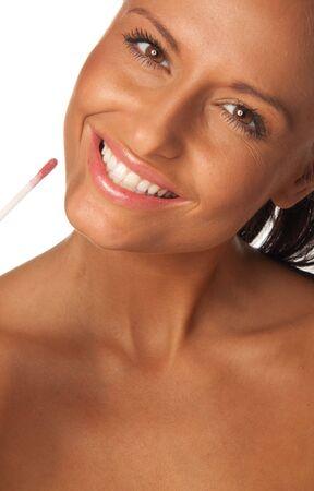 Beautiful young woman applying red lip gloss Stock Photo - 7726588