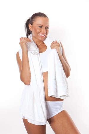 Fitness young woman with water bottle in hand and towel around her neck photo