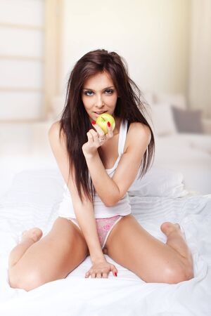 sexy brunette wearing sexy pyjama on white bed holding apple  photo
