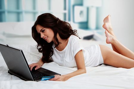 room access: Beautiful woman lying on bed with a laptop and credit card