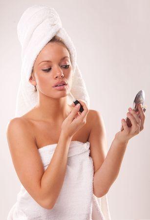 lip gloss: Portrait of young woman applying lip gloss Stock Photo