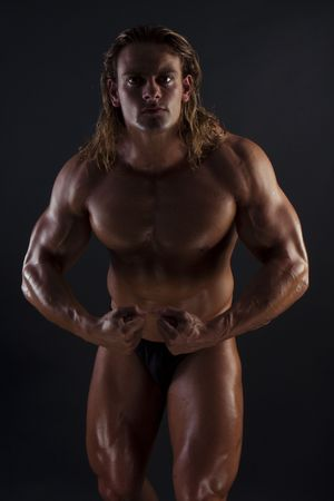 Athletic sexy male body builder with the blonde long hair. on black background Stock Photo - 8015812