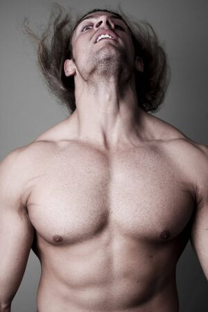 Athletic sexy male body builder with the blonde long hair. on black background photo