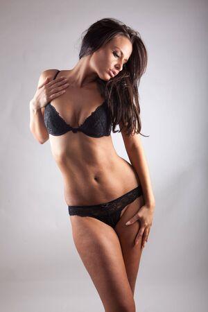 Seksowny kobieta. Czarny bielizna na szarym tle