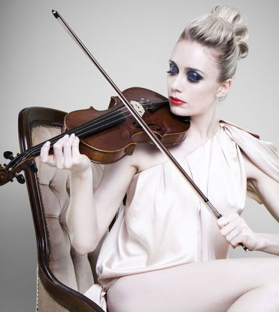Glamorous sexy young woman playing violin, light studio background. Stock Photo - 8305223
