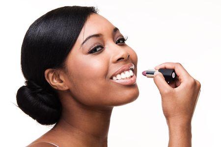 Portrait of a beautiful african black woman getting ready applying lipstick photo