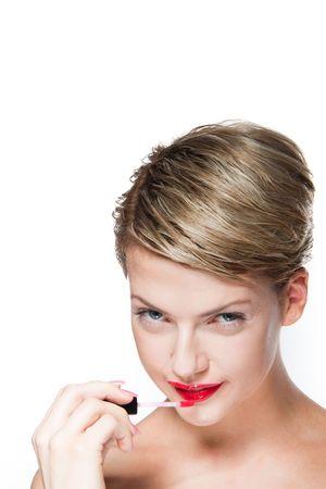 Portrait of young woman applying lip gloss Stock Photo - 8269449