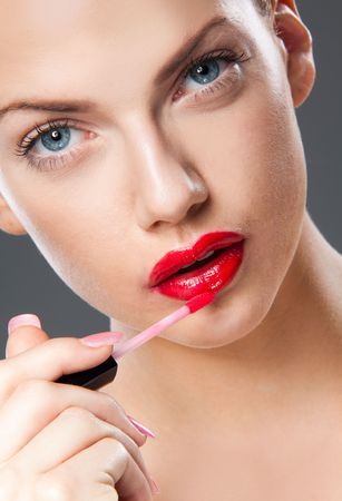 puckering lips: Portrait of young woman applying lip gloss Stock Photo