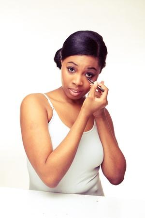 african beauty woman applying makeup on her eye  photo