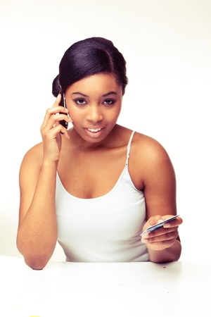 african woman speaking over the phone , paying using  credit card  photo
