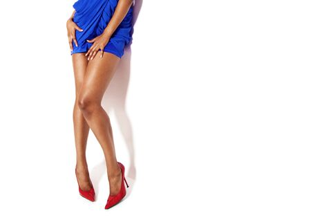 african american ethnicity: sexy black womans legs  wearing blue dress and red shoes , on white  Stock Photo