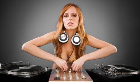 Beautiful DJ girl on decks on the party with plain background  photo