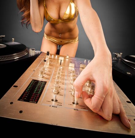 closeup mixer - Beautiful DJ girl on decks on the party with plain background  photo
