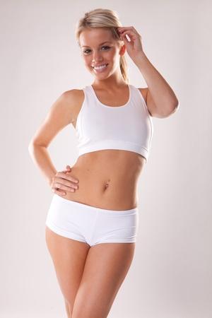 vientre femenino: Joven rubia hermosa en prendas de vestir de blanco fitness  Foto de archivo