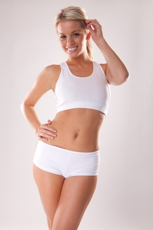 Young beautiful blonde woman in white fitness clothing  Фото со стока