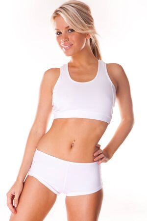 toned: Young beautiful blonde woman in white fitness clothing  Stock Photo