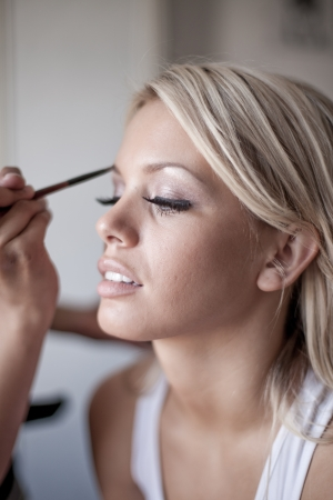 makeup a brush: Young beautiful bride applying wedding make-up by professional make-up artist