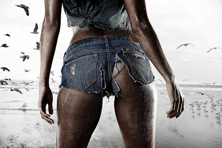 Sexy woman standing on the beach wearing wet ripped tiny booty shorts Фото со стока