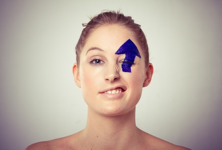 Portrait of smiling young blond haired woman with upward pointing arrow painted over eye, white studio background. photo