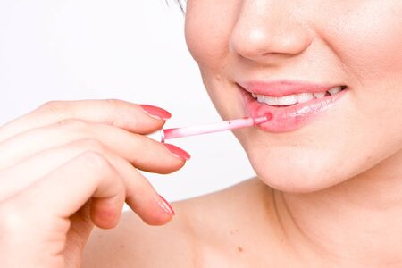 Portrait of young woman applying lip gloss Stock Photo - 8517997