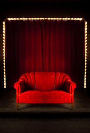 Kurtyna Czerwony pokój z sofa z przodu, czerwone sofa na stole montażowym w theatre Zdjęcie Seryjne