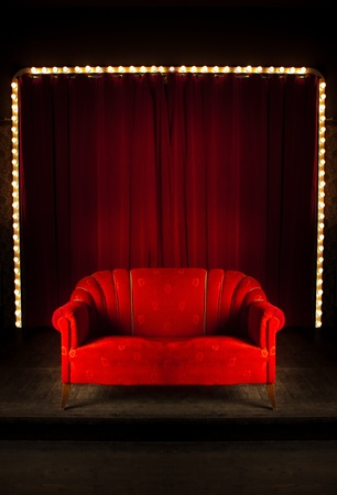 front room: Red curtain room with the sofa on the front , red sofa on the stage in theatre