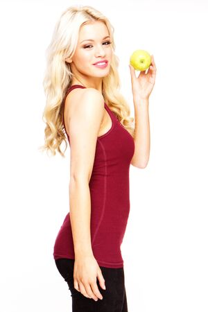 blonde sexy woman smiling holding fresh green apple  photo