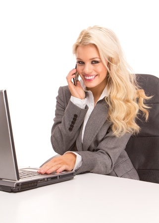 Portrait of an sexy business woman sitting by a desk and laptop speaking over the phone , smiling