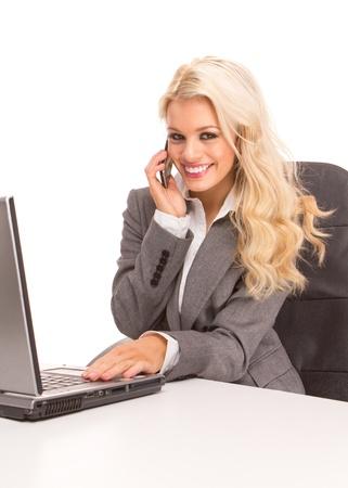 secretaria sexy: Retrato de una mujer de negocios sexy sentado en un escritorio y port�til que hablando por tel�fono, sonriendo