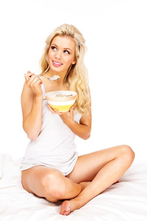 Sexy Woman sitting on bed eating cereal smiling photo