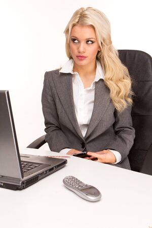 Young beautiful business lady having a rest at the working place. sending private message photo