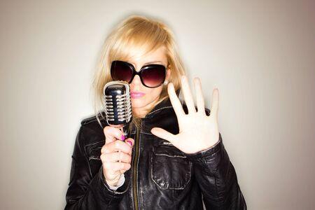 blonde woman holding a retro microphone wearing black jacket , singing rockstar photo