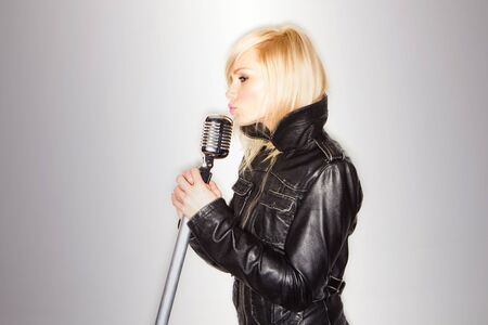 blonde woman holding a retro microphone wearing black jacket , singing rockstar photo