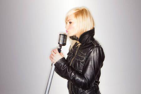 rocker girl: rubia mujer sosteniendo un micr�fono retro vistiendo la camiseta, cantando rockstar