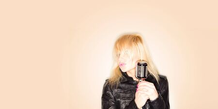 blonde woman holding a retro microphone wearing black jacket , singing rockstar Stock Photo - 8834463