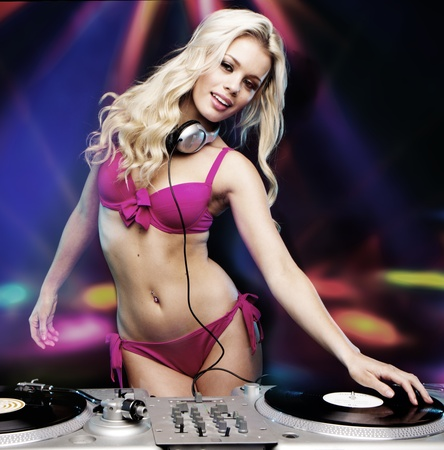 sexy headphones: Beautiful DJ girl on decks on the party wearing pink bikini