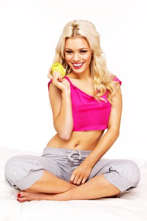 blonde smiling girl holding green apple , wearing pink top , sitting on a bed cover in studio Stock Photo - 8929190