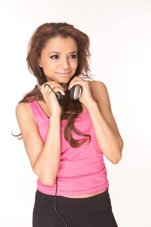 Young woman in pink listening music on white background  Stock Photo - 8940990