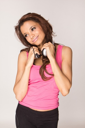 Young woman in pink listening music on white background  photo