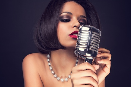 Beautiful singer singing with a retro microphone photo